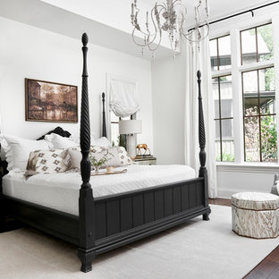 This is an example of a traditional master bedroom in Nashville with white walls, dark hardwood flooring and no fireplace.