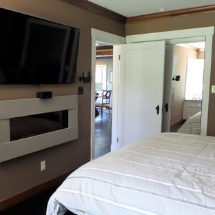 Diseño de dormitorio principal, de estilo americano, de tamaño medio, con paredes beige, chimeneas suspendidas, marco de chimenea de hormigón, suelo de madera oscura y suelo marrón