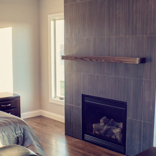 Large modern master bedroom in Boise with beige walls, dark hardwood floors, a standard fireplace and a tile fireplace surround.