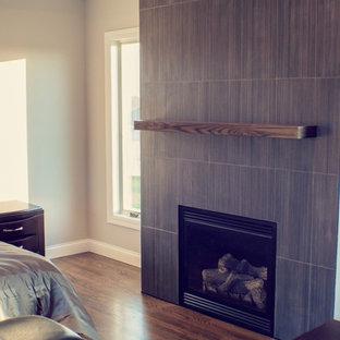 Réalisation d'une grand chambre parentale minimaliste avec un mur beige, un sol en bois foncé, une cheminée standard et un manteau de cheminée en carrelage.