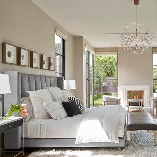 ダラスのコンテンポラリースタイルのおしゃれな寝室 (ベージュの壁、無垢フローリング、標準型暖炉、茶色い床)