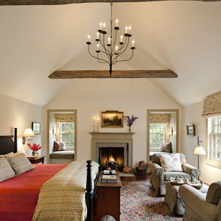 Стильный дизайн: огромная хозяйская спальня в стиле кантри с белыми стенами, паркетным полом среднего тона, стандартным камином и фасадом камина из камня - последний тренд