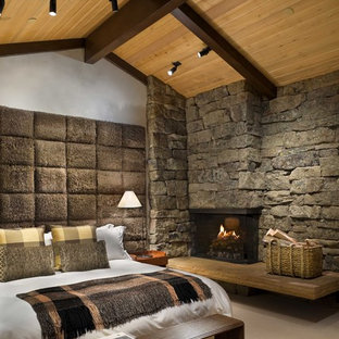 Idéer för ett mellanstort rustikt huvudsovrum, med en spiselkrans i sten, en öppen hörnspis, vita väggar och betonggolv
