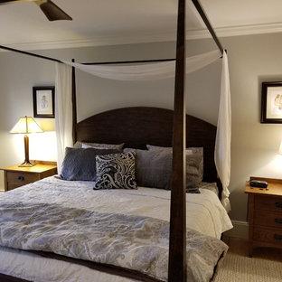 На фото: хозяйская спальня среднего размера в классическом стиле с серыми стенами, светлым паркетным полом и подвесным камином с