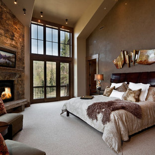 This is an example of a country bedroom in Salt Lake City with a corner fireplace and a stone fireplace surround.