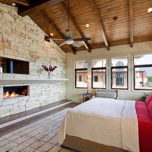 Foto de dormitorio mediterráneo con paredes beige, suelo de madera oscura, chimenea lineal y marco de chimenea de piedra