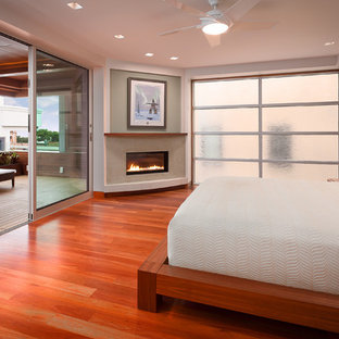 This is an example of a medium sized contemporary master bedroom in Los Angeles with a corner fireplace, multi-coloured walls, medium hardwood flooring and a plastered fireplace surround.