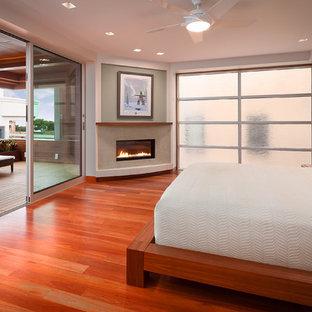 Стильный дизайн: хозяйская спальня среднего размера в современном стиле с угловым камином, разноцветными стенами, паркетным полом среднего тона и фасадом камина из штукатурки - последний тренд