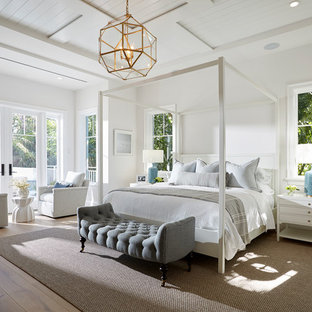 Example of a beach style master medium tone wood floor and brown floor bedroom design in Miami with white walls