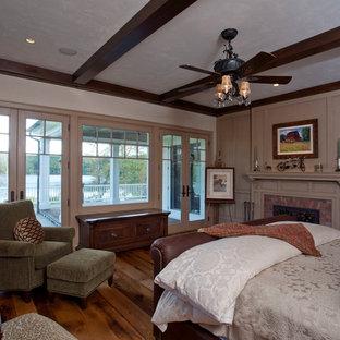 Inspiration för stora lantliga huvudsovrum, med beige väggar, mellanmörkt trägolv, en standard öppen spis och en spiselkrans i tegelsten