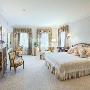 ニューヨークのトラディショナルスタイルのおしゃれな主寝室 (ベージュの壁、カーペット敷き、標準型暖炉) のインテリア