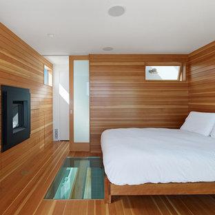 На фото: маленькая хозяйская спальня в современном стиле с горизонтальным камином, паркетным полом среднего тона и фасадом камина из дерева с