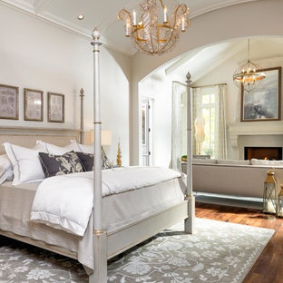 ナッシュビルの広い地中海スタイルのおしゃれな主寝室 (ベージュの壁、濃色無垢フローリング、標準型暖炉、漆喰の暖炉まわり、茶色い床) のインテリア