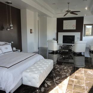 ラスベガスの大きいコンテンポラリースタイルのおしゃれな主寝室 (白い壁、大理石の床、標準型暖炉、石材の暖炉まわり、茶色い床)