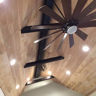 Diseño de dormitorio principal, campestre, grande, con paredes grises, suelo de madera en tonos medios, chimenea tradicional, marco de chimenea de madera y suelo marrón