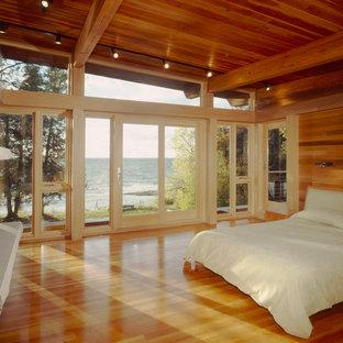 Imagen de dormitorio principal, actual, de tamaño medio, con suelo de madera clara, chimenea tradicional y marco de chimenea de piedra