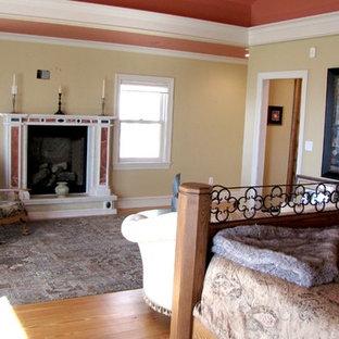ボストンの大きいヴィクトリアン調のおしゃれな主寝室 (標準型暖炉、黄色い壁、合板フローリング、漆喰の暖炉まわり、茶色い床)