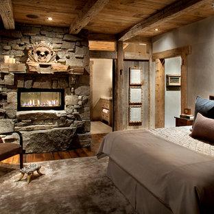 Ispirazione per una camera da letto stile rurale con cornice del camino in pietra, camino bifacciale e pavimento in legno massello medio