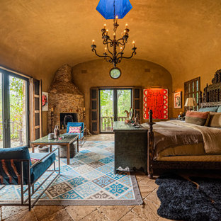 Bedroom - southwestern master brown floor and vaulted ceiling bedroom idea in Houston with brown walls, a corner fireplace and a stone fireplace