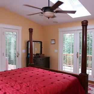Ejemplo de dormitorio principal, tradicional renovado, de tamaño medio, con paredes amarillas y suelo de madera en tonos medios