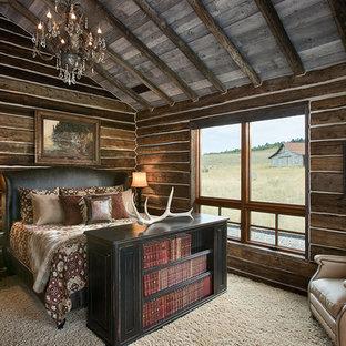 Ejemplo de dormitorio principal, rural, grande, con moqueta, paredes marrones, estufa de leña, marco de chimenea de piedra y suelo beige