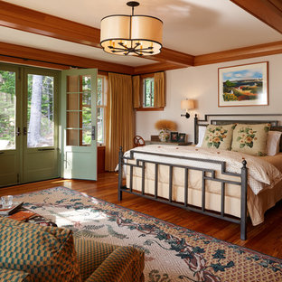 This is an example of an arts and crafts master bedroom in Portland Maine with beige walls and medium hardwood floors.
