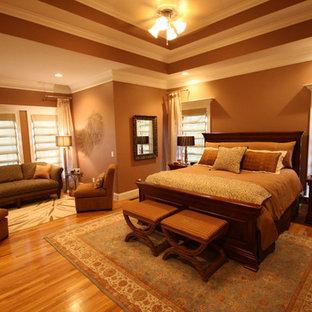 Modelo de dormitorio principal, clásico, grande, sin chimenea, con paredes marrones y suelo de madera en tonos medios