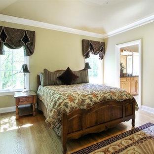 Foto de dormitorio principal, clásico, grande, sin chimenea, con paredes beige, suelo de madera clara, marco de chimenea de ladrillo y suelo beige