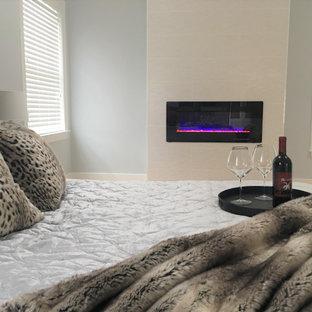 Foto de dormitorio principal, minimalista, grande, con paredes azules, suelo de madera clara, chimeneas suspendidas, marco de chimenea de baldosas y/o azulejos y suelo amarillo