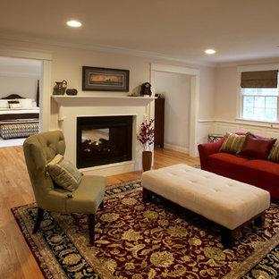 Modelo de dormitorio principal, tradicional, grande, con paredes beige, suelo de madera clara, chimenea de doble cara y marco de chimenea de madera