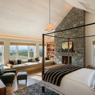 Example of a large country master medium tone wood floor and brown floor bedroom design in Other with beige walls, a standard fireplace and a stone fireplace
