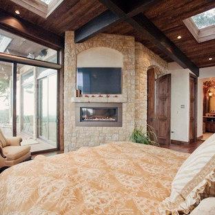 Foto på ett mellanstort amerikanskt huvudsovrum, med beige väggar, mellanmörkt trägolv, en bred öppen spis och en spiselkrans i sten