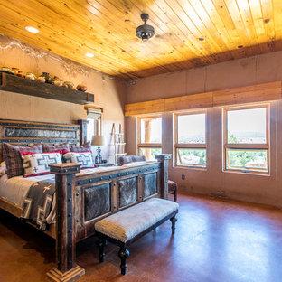 Cette image montre une chambre parentale sud-ouest américain de taille moyenne avec un mur orange, béton au sol et un sol rouge.