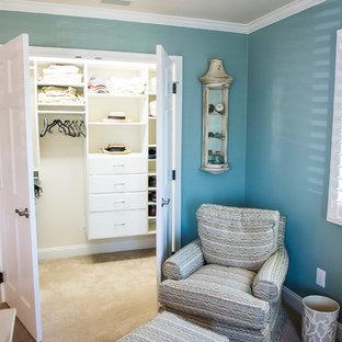 Modelo de dormitorio principal, costero, de tamaño medio, sin chimenea, con paredes azules y moqueta