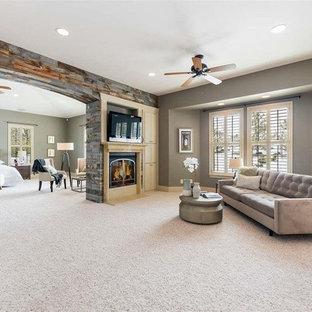 Modelo de dormitorio principal, clásico renovado, grande, con paredes grises, moqueta, chimenea de doble cara, marco de chimenea de madera y suelo multicolor