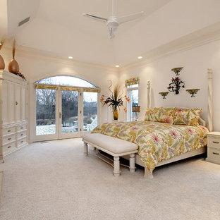 Modelo de dormitorio principal, exótico, grande, con paredes blancas, moqueta, chimenea tradicional y marco de chimenea de piedra