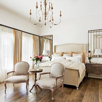 Elegant medium tone wood floor and brown floor bedroom photo in Phoenix with white walls