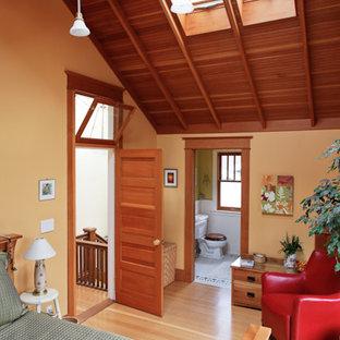 Foto de dormitorio principal, de estilo americano, extra grande, con paredes amarillas y suelo de madera clara