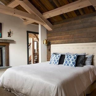 Пример оригинального дизайна: хозяйская спальня среднего размера в стиле рустика с белыми стенами, ковровым покрытием, двусторонним камином, бежевым полом и фасадом камина из дерева
