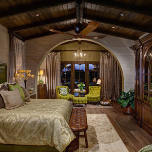 Photo of a large mediterranean master bedroom in Orlando with beige walls, dark hardwood floors and brown floor.