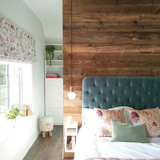 Modelo de dormitorio principal, campestre, de tamaño medio, con paredes verdes y suelo vinílico