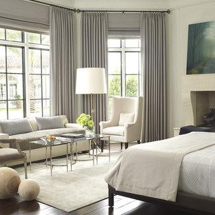 Modelo de dormitorio principal, mediterráneo, extra grande, con paredes blancas, suelo de madera oscura, chimenea tradicional, marco de chimenea de piedra y suelo marrón
