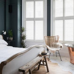 サセックスの中くらいの北欧スタイルのおしゃれな主寝室 (青い壁、淡色無垢フローリング、茶色い床、格子天井) のインテリア