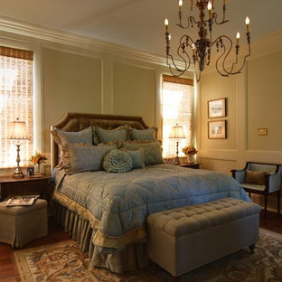 This is an example of a mid-sized victorian master bedroom in New Orleans with beige walls, dark hardwood floors and brown floor.