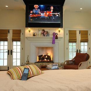 Imagen de dormitorio principal, campestre, grande, con paredes blancas, suelo de madera en tonos medios, chimenea tradicional y marco de chimenea de yeso