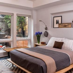 Diseño de dormitorio actual, de tamaño medio, sin chimenea, con paredes grises, suelo de cemento y suelo gris