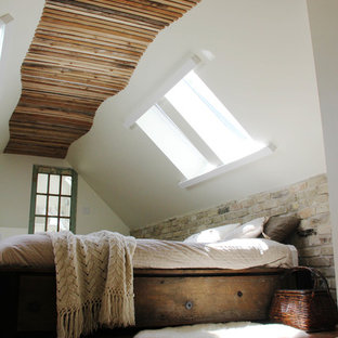 Exemple d'une chambre montagne avec un mur blanc et un sol en bois brun.