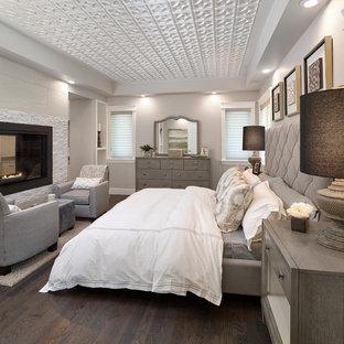 Diseño de dormitorio principal, tradicional renovado, grande, con paredes grises, suelo de madera oscura, chimenea de doble cara y marco de chimenea de piedra
