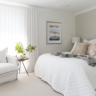 Large beach style master bedroom in Gold Coast - Tweed with white walls, carpet and grey floor.