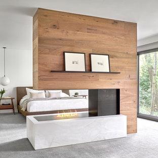 На фото: большая хозяйская спальня в современном стиле с белыми стенами, ковровым покрытием, двусторонним камином и серым полом